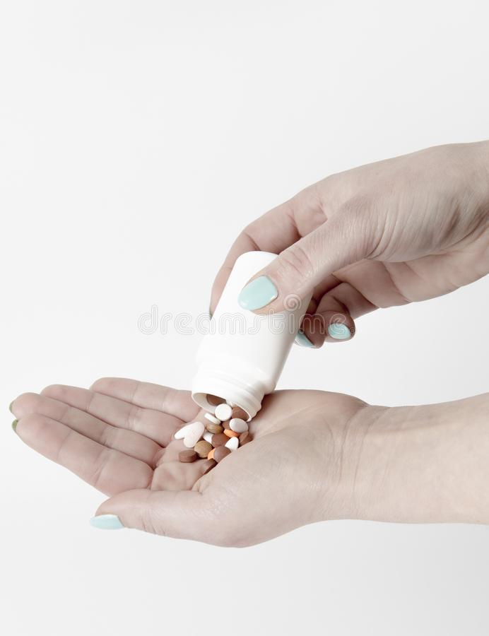 Разлейте таблетки от белой бутылки лекарства в человеческую руку стоковая фотография