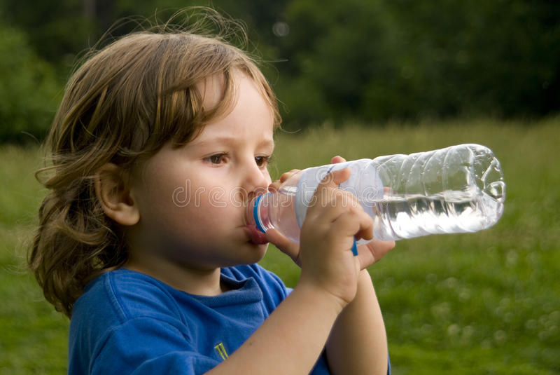 разлитая по бутылкам питьевая вода мальчика стоковое изображение rf