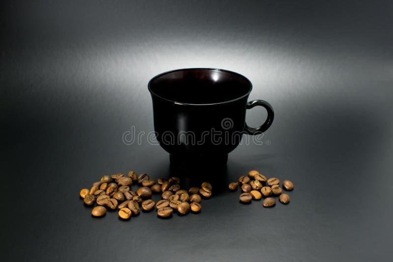 Разлитые кофейные зерна с черной чашкой стоковые фотографии rf