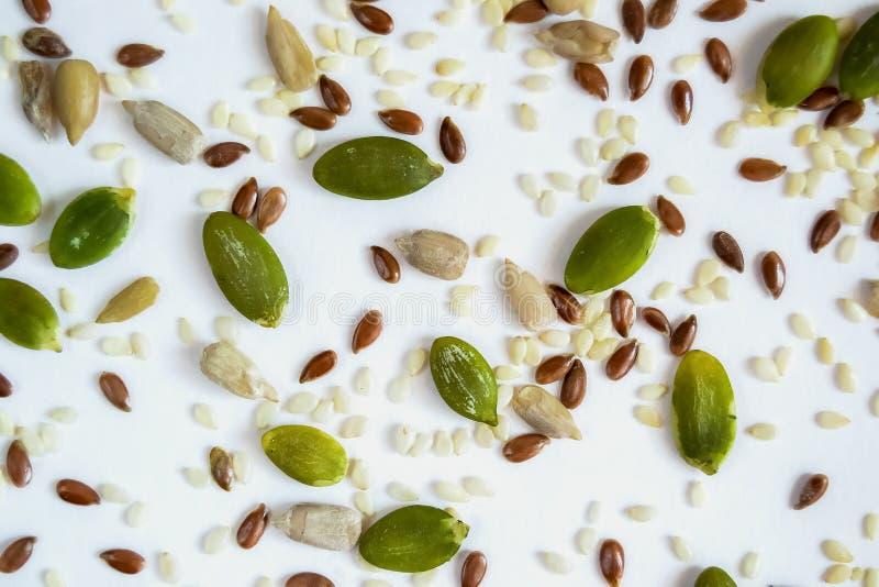 Разлитые семена льна тыквы и солнцецвета на белой предпосылке стоковая фотография rf