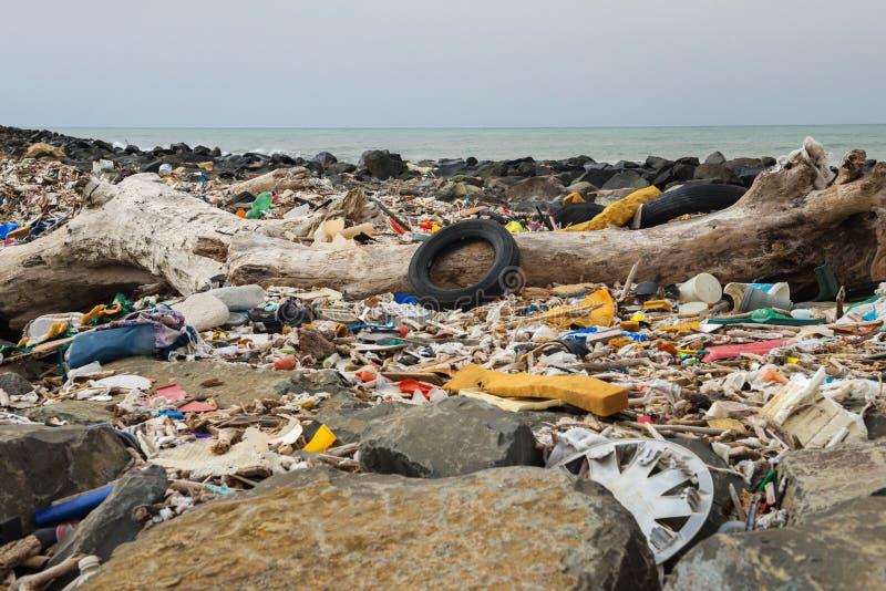 Разлитый отброс на пляже около большого города Пустые используемые грязные пластиковые бутылки и другой отброс environmental стоковое изображение rf