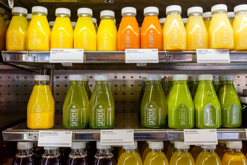 Разлитый по бутылкам сок в холодильнике полки стоковые фотографии rf
