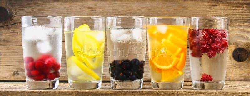 Различная вода вытрезвителя в стеклах, различных вкусах, ягодах, плодоовощах стоковые изображения