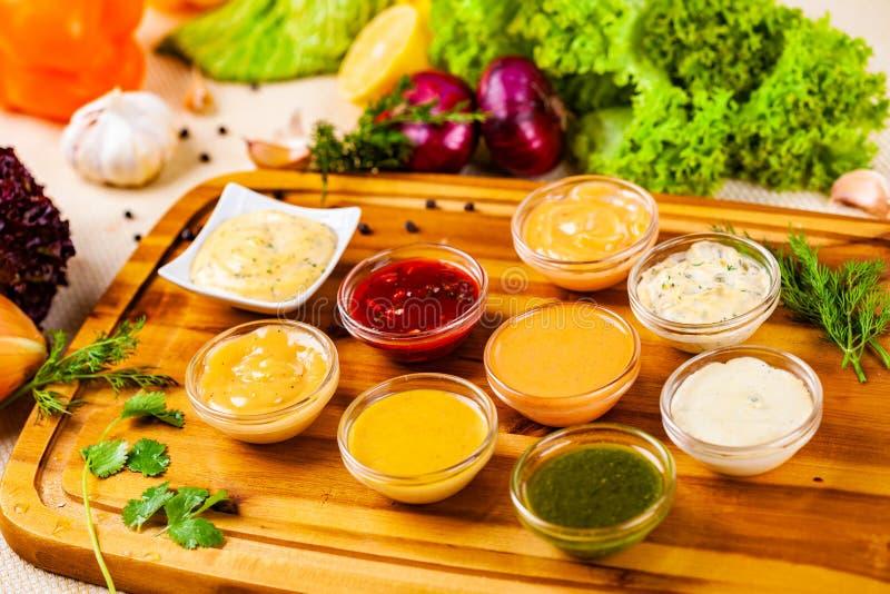 Различные ассортименты соусов на деревянной доске резания стоковое изображение