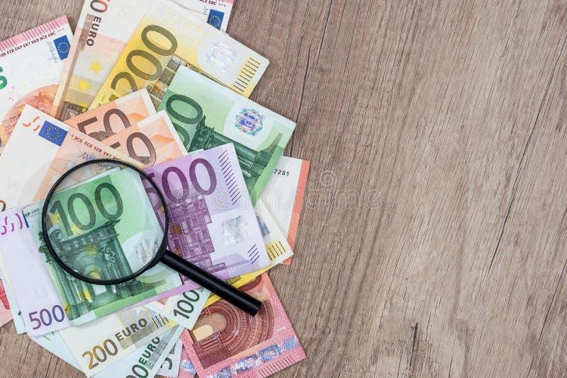Различные банкноты евро под лупой стоковые изображения rf