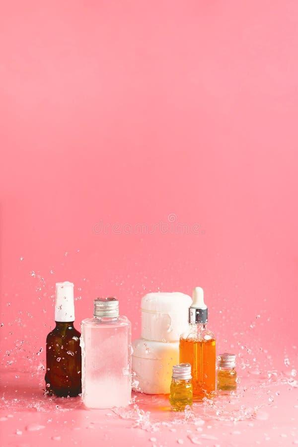 Различные бутылки, опарникы и контейнеры с косметиками на пинке с брызгать воды стоковое фото