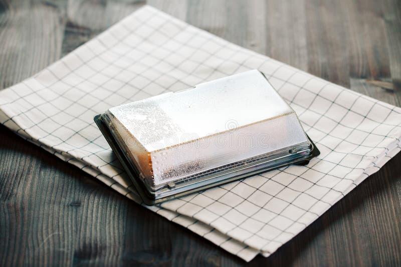 Различные виды горячих зажаренных кренов служили в пластичной коробке суш на таблице стоковая фотография