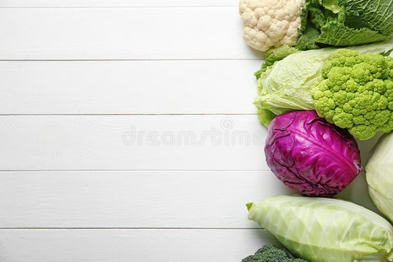 Различные виды капусты на белой деревянной предпосылке стоковое изображение rf