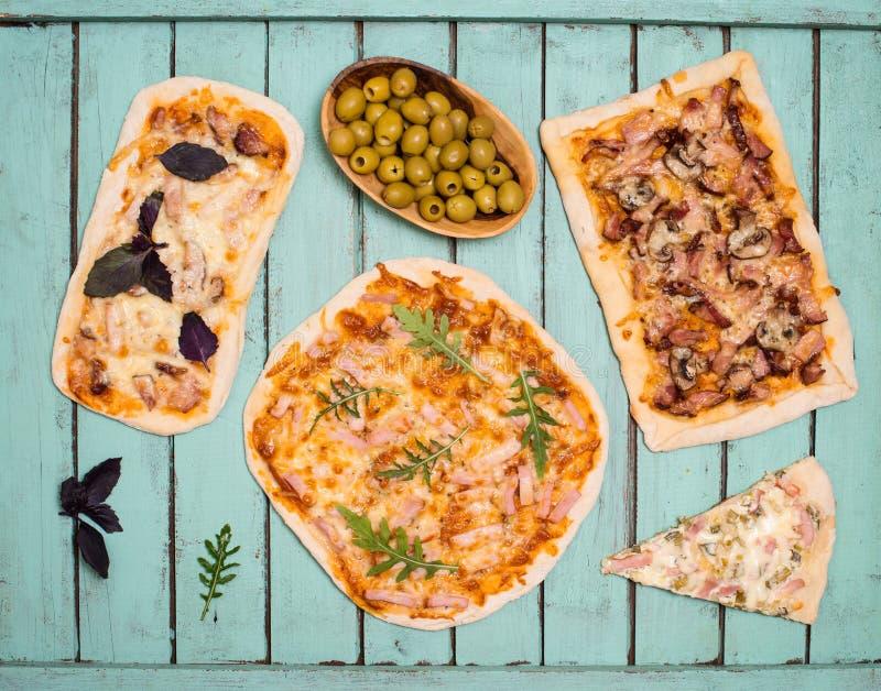 Различные виды небольшой пиццы на деревенской затрапезной шикарной предпосылке Различная домодельная пицца, официальныйо обед дом стоковое изображение