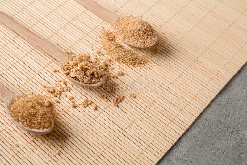 Различные виды сахара в деревянных ложках на бамбуковой циновке стоковое изображение rf
