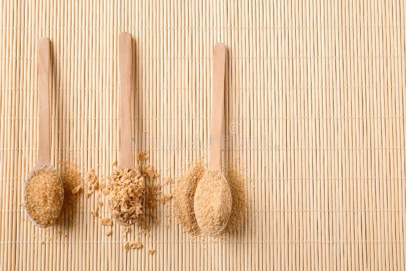 Различные виды сахара в деревянных ложках на бамбуковой циновке стоковые фото