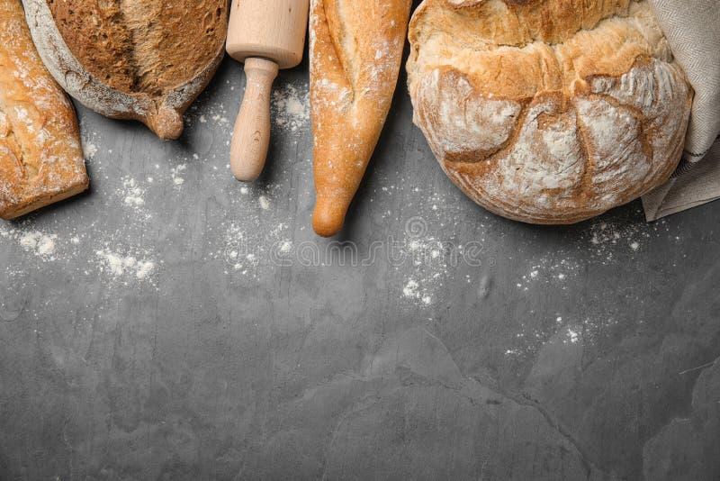 Различные виды свежего хлеба на серой таблице, плоское положение стоковые фотографии rf