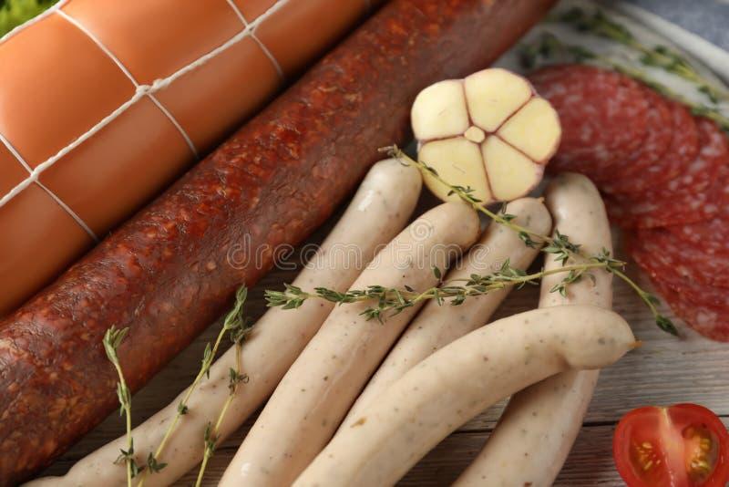 Различные виды сосисок на деревянной доске, крупном плане стоковые изображения rf