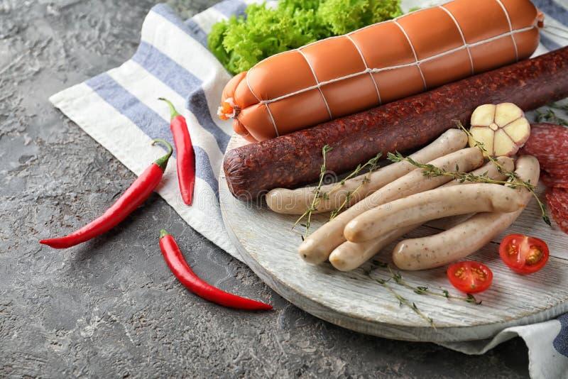 Различные виды сосисок на деревянной доске стоковые фото