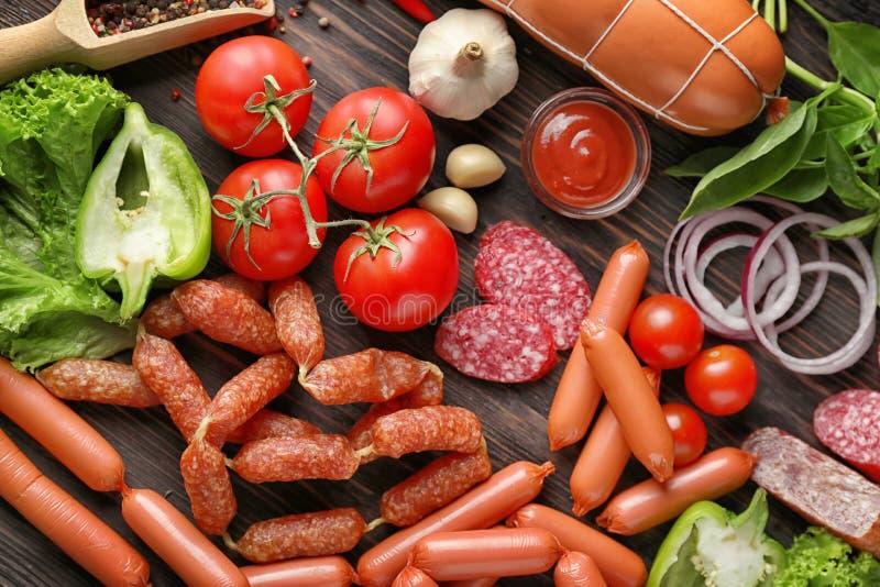 Различные виды сосисок с соусом и овощами на деревянной предпосылке стоковое фото