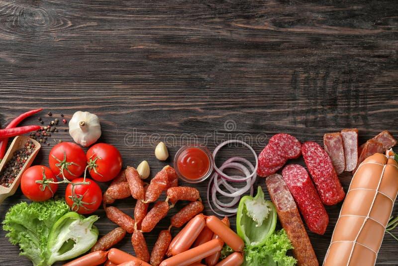 Различные виды сосисок с соусом, специями и овощами на деревянной предпосылке стоковые фотографии rf