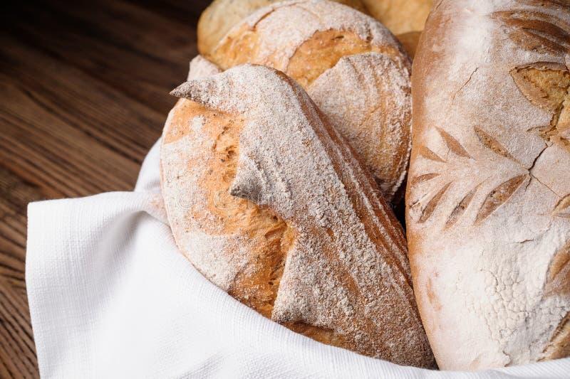 Различные виды хлеба и багетов в плетеной корзине на деревянном столе стоковые фотографии rf