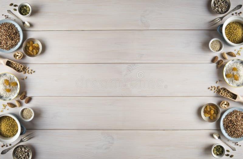 Различные гайки, хлопья, изюминки на плитах на деревянном столе Кедр, анакардия, фундук, грецкие орехи, миндалины, семена тыквы,  стоковые фото