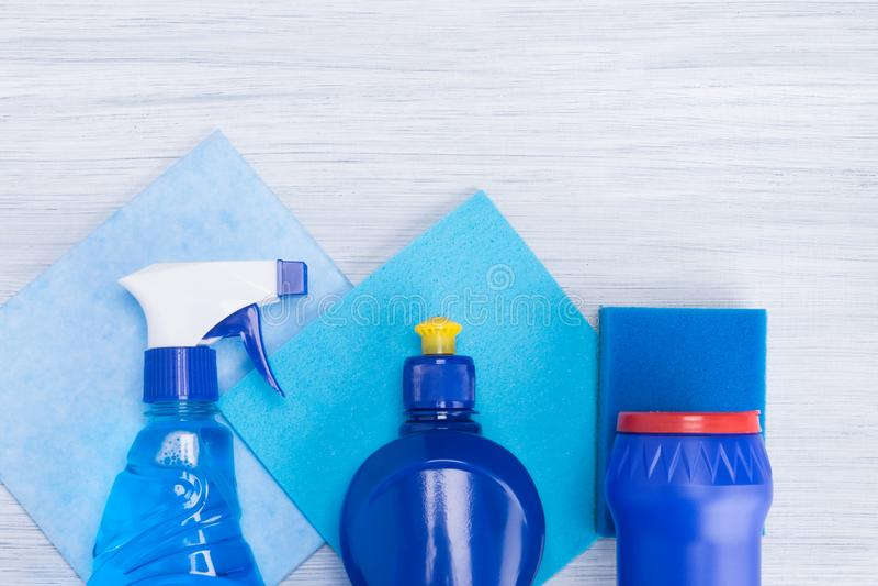 Различные голубые бутылки с тензидами для очищать на предпосылке голубых ветошей стоковое фото