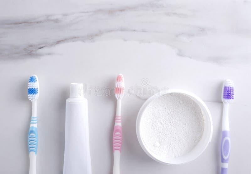 Различные инструменты для чистить зуб щеткой на белой поверхности, взгляд сверху Зубная паста, порошок зуба, зубные щетки, пустой стоковая фотография