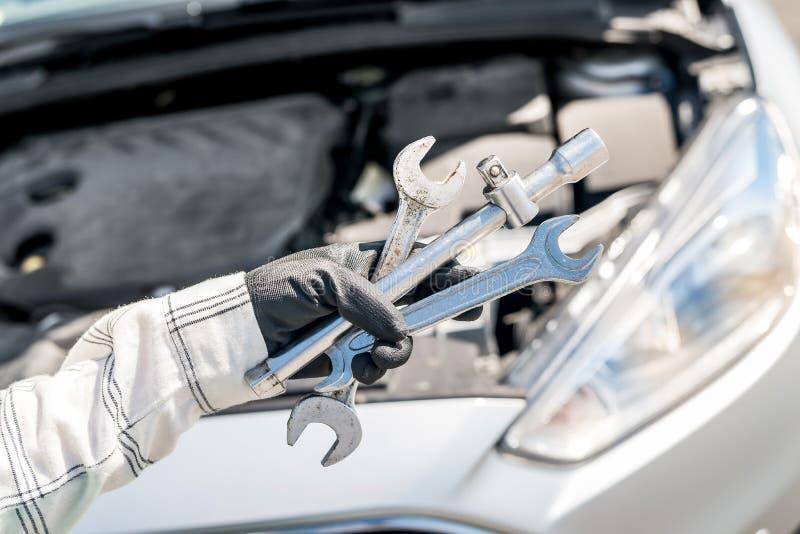 Различные ключи и гаечные ключи в руке над автомобилем стоковая фотография