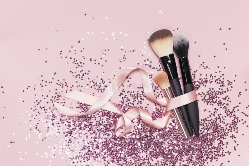 Различные косметические щетки макияжа с розовой лентой и голографическим confetti яркого блеска в форме звезд на розовой квартире стоковые изображения