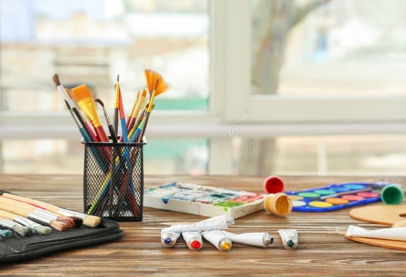 Различные краски с щетками на таблице около окна стоковые фотографии rf
