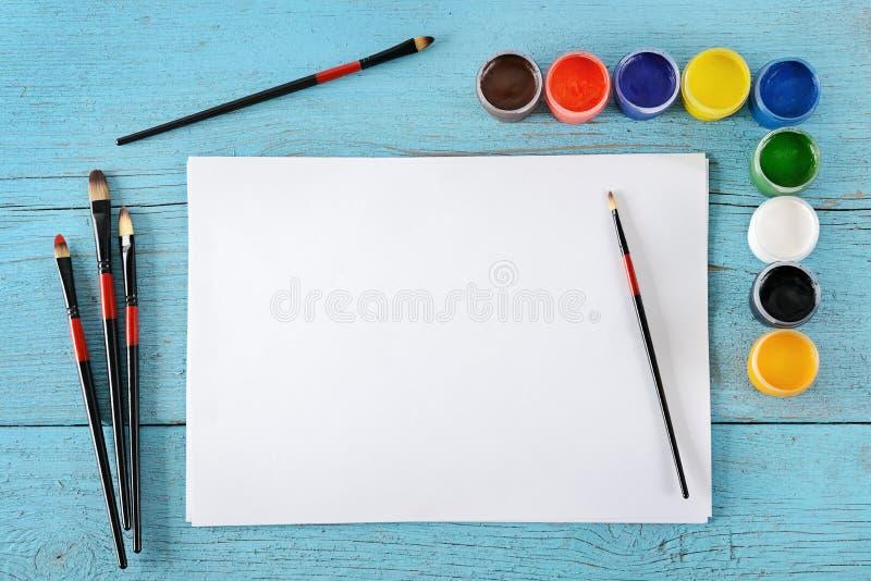 Различные краски, щетки, белая бумага листов на деревянном голубом backg стоковые изображения rf
