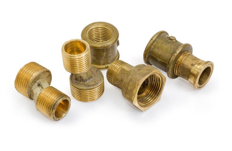 Различные латунные штуцеры трубы и компоненты трубопровода на белом b стоковая фотография
