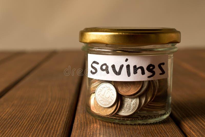 Различные монетки в стеклянном опарнике Концепция сбережений стоковые фотографии rf
