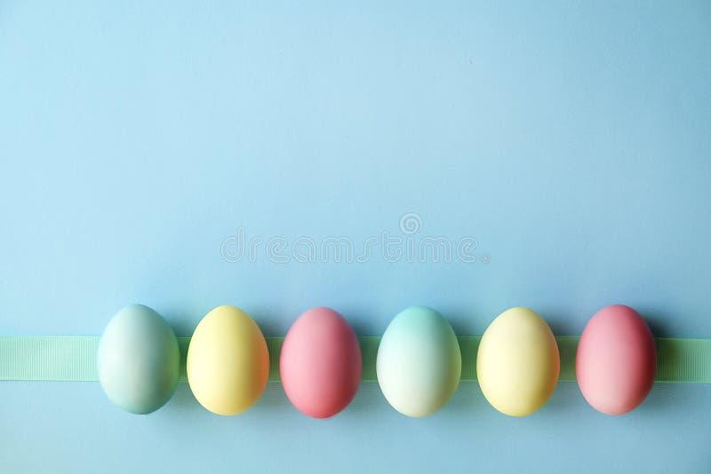Различные пасхальные яйца пастельного цвета клали и аранжировали в красивом составе с белыми wildflowers Поздравительная открытка стоковое фото rf