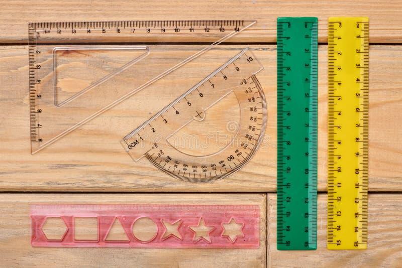 Различные пластиковые правители на деревянной предпосылке стоковое изображение