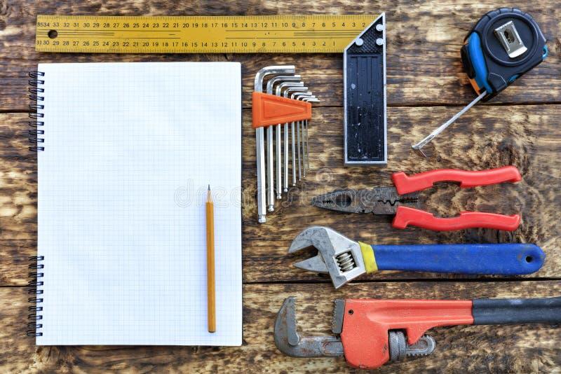 Различные ручные резцы и пустой блокнот с карандашем на старой деревянной предпосылке стоковые фото