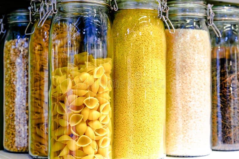 Различные сырцовые хлопья, зерна, фасоли и макаронные изделия для здоровый варить в опарниках стекла на полке кухни Чистая еда, в стоковое фото