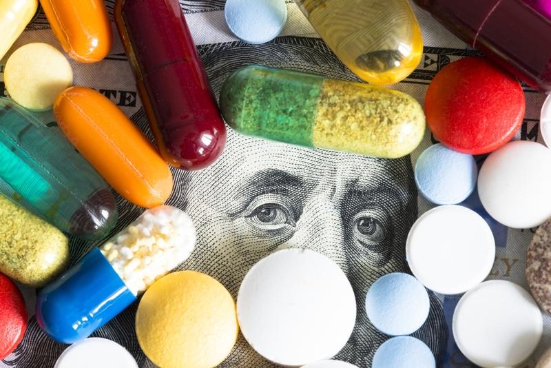 Различные таблетки на американских банкнотах долларов, цене концепции медицины стоковое изображение