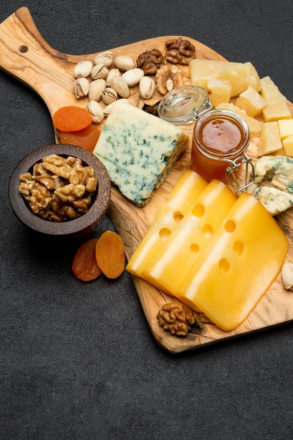 Различные типы сыра - бри, камамбера, рокфора и чеддера на деревянной доске стоковые изображения