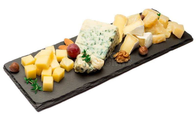 Различные типы сыра - бри, камамбера, рокфора и чеддера на каменной доске стоковое фото rf