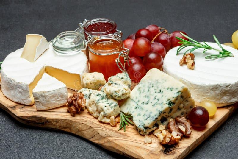 Различные типы сыра и варенья на деревянной разделочной доске стоковое фото rf