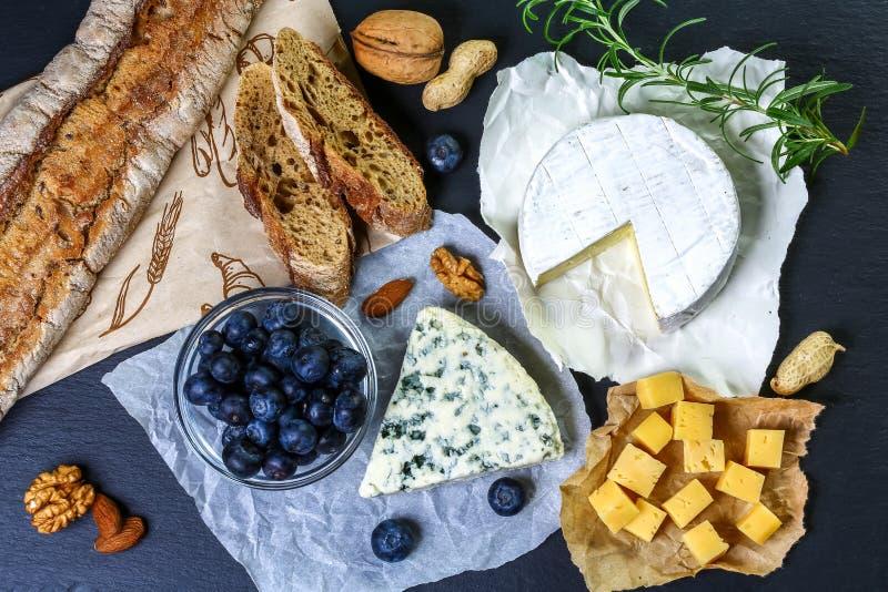 Различные типы сыра на деревенской каменной доске Дизайн меню горизонтальный Взгляд сверху стоковые изображения
