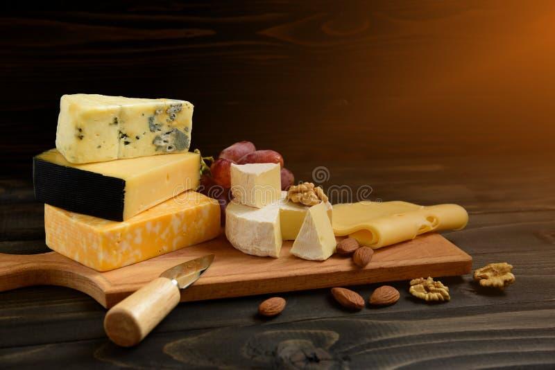 Различные типы сыра на деревенской таблице стоковое фото