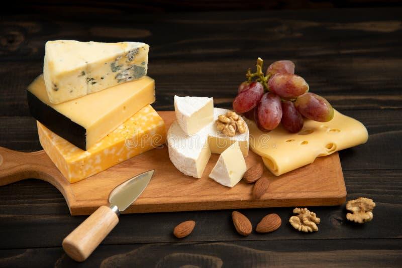 Различные типы сыра на деревенской таблице стоковые изображения rf