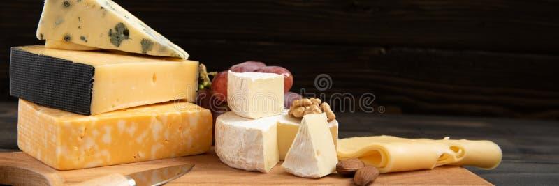 Различные типы сыра на деревенской таблице стоковое изображение
