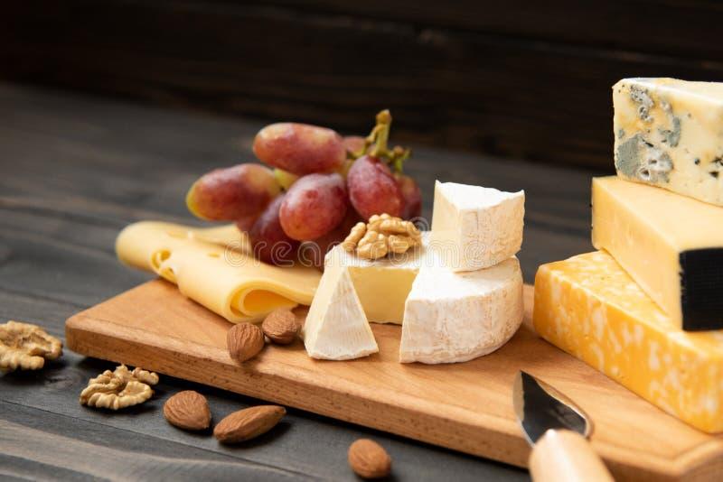 Различные типы сыра на деревенской таблице стоковая фотография