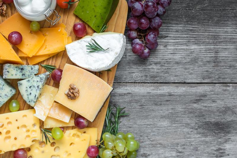 Различные типы сыра на разделочной доске с виноградиной и гайками над деревенским деревянным столом, взгляд сверху стоковое изображение