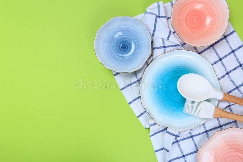 Различные утвари кухни, плиты и полотенце на зеленой предпосылке r стоковая фотография rf