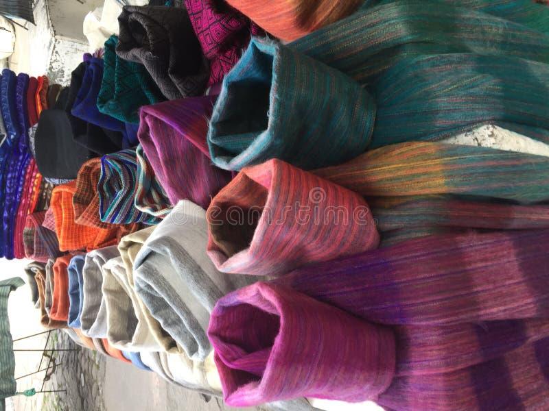 Различные шарфы в нескольких цветов и ткани для продажи на стойке рынка Otavalo, эквадора стоковое фото