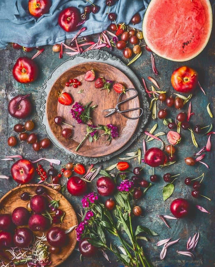 Различные ягоды и плодоовощи лета на деревенском постаретом кухонном столе с цветками и плитами, взгляд сверху, плоско положением стоковая фотография rf