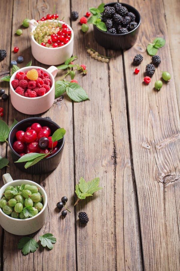 Различные ягоды на старой деревянной предпосылке стоковые изображения