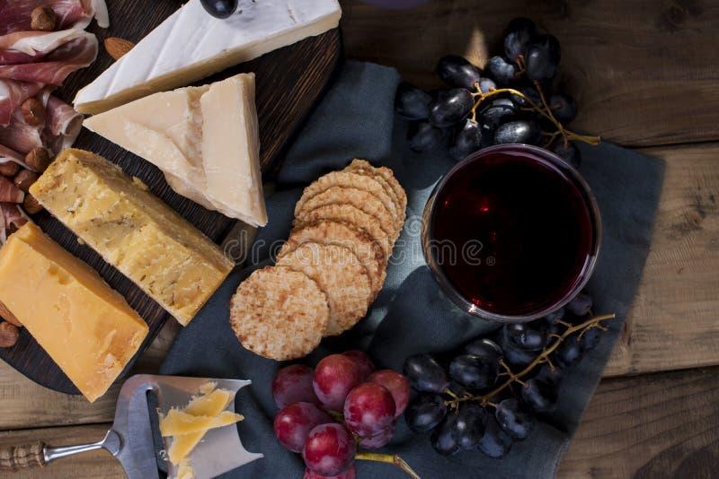 Различный голландский сыр, виноградины и ветчина, закуски для партии и красное вино скопируйте космос стоковое изображение
