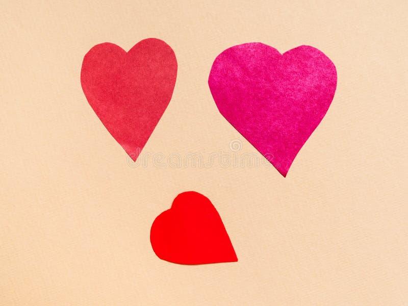 3 различных сердца отрезанного от красных бумаг на беже стоковое фото rf